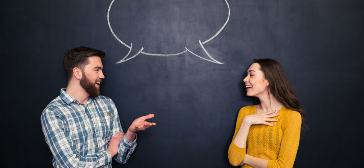 Happy couple talking over chalkboard background with drawn dialogue
